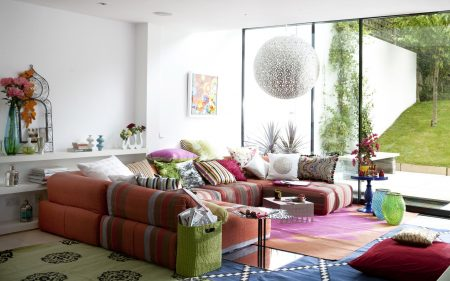 White living room glass wall floor to ceiling windows low Bedouin style dark red sofa assorted eclectic cushions rugs and floor cushions sphere ceiling lamp shade L etc 08/2009 pub orig