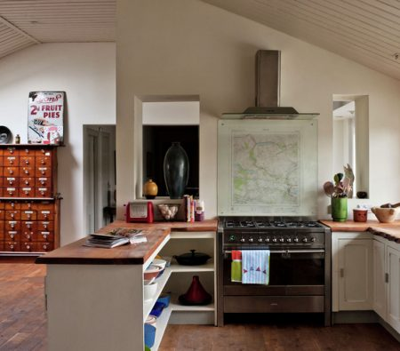Neutral open plan room / kitchen area high gabled ceiling / roof with tongue and groove panelling, peninsular with wood worktops doubles as bookcase storage, floorboards, window, sink, glass splashback and map, range cooker, extractor fan hood CH&I 02/2013